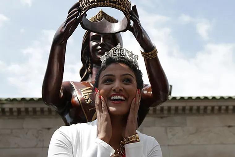 Miss America Nina Davuluri poses with the Miss America statue in front of Boardwalk Hall in Atlantic City, NJ on April 28, 2014. ( DAVID MAIALETTI / Staff Photographer )