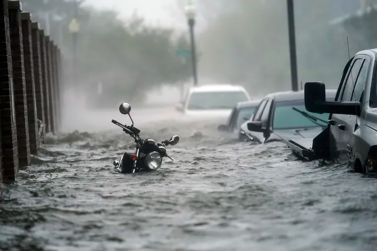 Cars and a motorcycle are underwater as water floods a street in Pensacola, Fla., on Wednesday.
