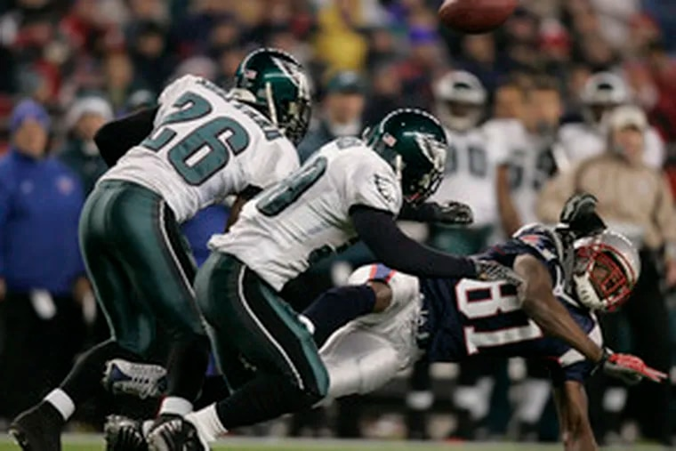 Lito Sheppard (26) and J.R. Reed break up a pass intended for Randy Moss against New England. Despite being out of the playoffs, the Eagles say they plan to play hard.