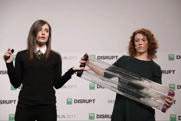 Bethany Edwards (left) and Anna Simpson demonstrate how the Lia pregnancy test is biodegradable by breaking up in water at TechCrunch Disrupt Berlin Tuesday. Lia Diagnostics were the overall winner of the competition.