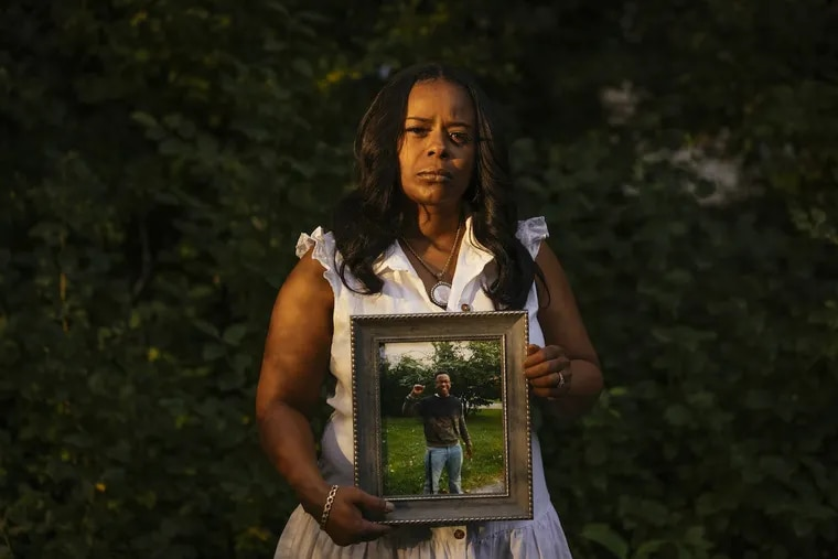 Rafiah Maxie holds a photo of her son, Jamal Clay, who died by suicide in May 2020.