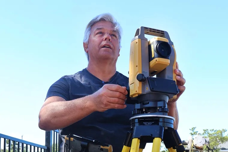 Former physics high school teacher James Huebner takes an angular measurement with his Theodolite as he works on a surveying job in the Long Beach Island community of Loveladies, N.J. on June 23, 2021 Photo: Tom Briglia