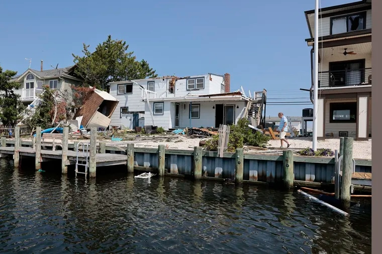 People begin assessing the damage left behind on  Arnold Blvd. in the High Bar Harbor section of Long Beach Township on Friday. Destructive storms that included tornados left their marks in both Pennsylvania and New Jersey