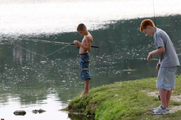 """Lucas Ecret (left) and Gregory Terry, both of Woodstown, N.J., fish in Memorial Lake. """"I love the fight of the fish,"""" Lucas says."""