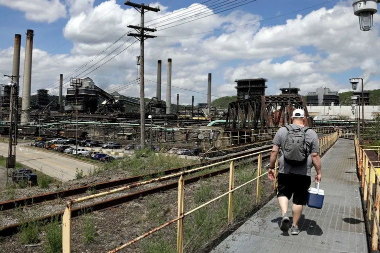 In this May 2, 2019 photo, a worker arrives for his shift at the U.S. Steel Clairton Coke Works in Clairton, Pa., part of the company's Mon Valley complex. The company is spending hundreds of millions updating its plants, amid worries that world demand for steel has slowed.