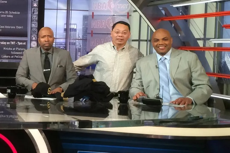 """Lin Wang (center) stands beside TNT analysts Charles Barkley (right) and Kenny Smith on the set of """"Inside the NBA."""""""