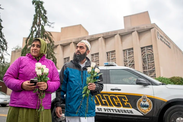 Samina Mohamedali, left, and her husband Kutub Ganiwalla, members of the Dawoodi Bohra Muslim community, both of North Hills, prepare to place flowers on a memorial in front of the Tree of Life Congregation, Sunday, Oct. 28, 2018, in Squirrel Hill neighborhood of Pittsburgh.