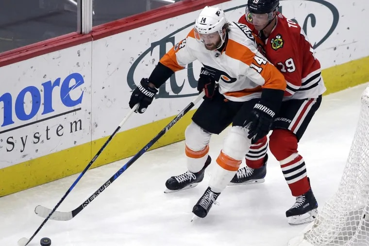 Flyers center Sean Couturier, left, controls the puck against Chicago Blackhawks center Jonathan Toews during the second period.