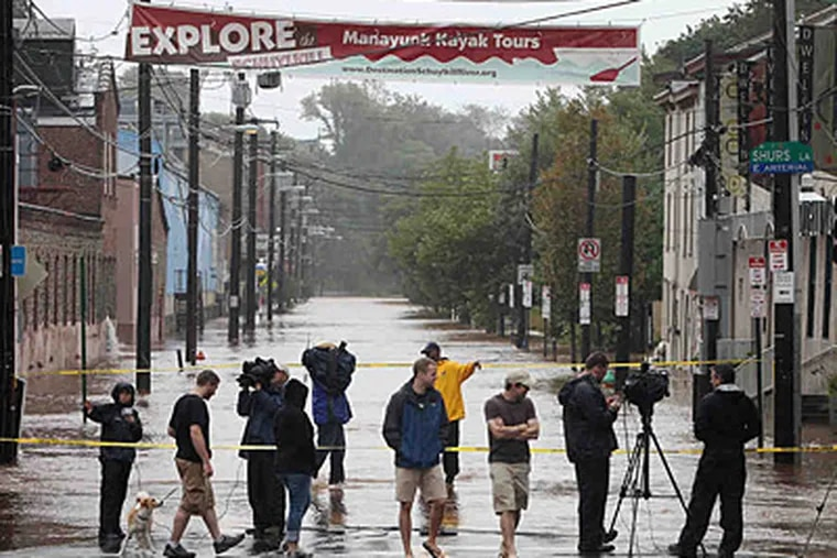 The local media gathered in Manayunk Sunday to turn their cameras on the only block of Main Street that had any flooding. (Alejandro A. Alvarez/Staff)