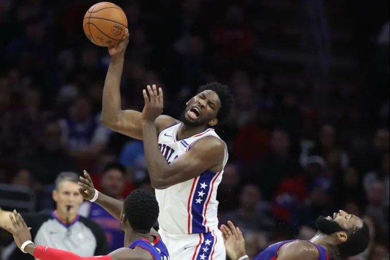 Joel Embiid, center, of the Sixers collides with Andre Drummond, right, of the Pistons in the 4th quarter at the Wells Fargo Center on Dec. 2, 2017.