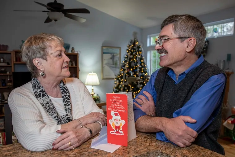Jeanne Smith, left, and Mike DeNardo, right, with the Christmas card they have been mailing back and forth to each other for the last 35 years, at Smith's Pemberton, NJ home on December 10, 2019.