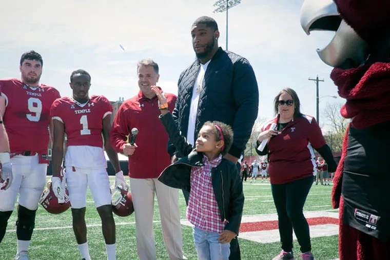 Leah Still tosses the game coin as father Devon watches Saturday, April 25, 2015, before Temple University's Cherry and White football game. (ED HILLE / Staff Photographer)