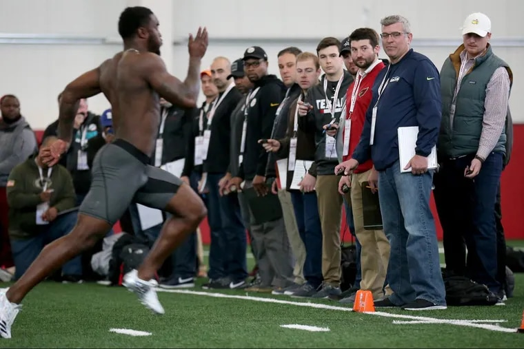 NFL personnel time the Owls' Sean Chandler, at left, as he runs the 40-yard dash as the Temple Owls hosts their annual NFL Pro Day in Philadelphia, PA on March 19, 2018.