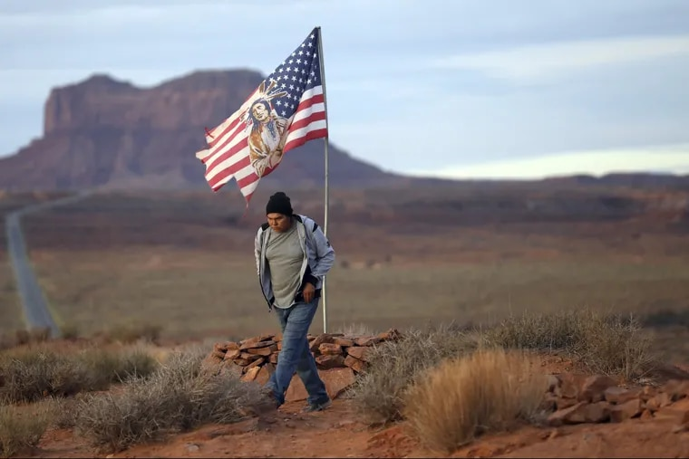 Brandon Nez displays his flag at near his jewelry stand in Monument Valley, Utah. As Native American tribes around the country fight for increased access to the ballot box, Navajo voters in one Utah county could tip the balance of power in the first general election since a federal judge ordered overturned their voting districts as illegally drawn to minimize native voices.