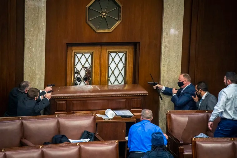 Security officers point weapons at a House chamber door as a mob of rioters storms the Capitol on Wednesday.