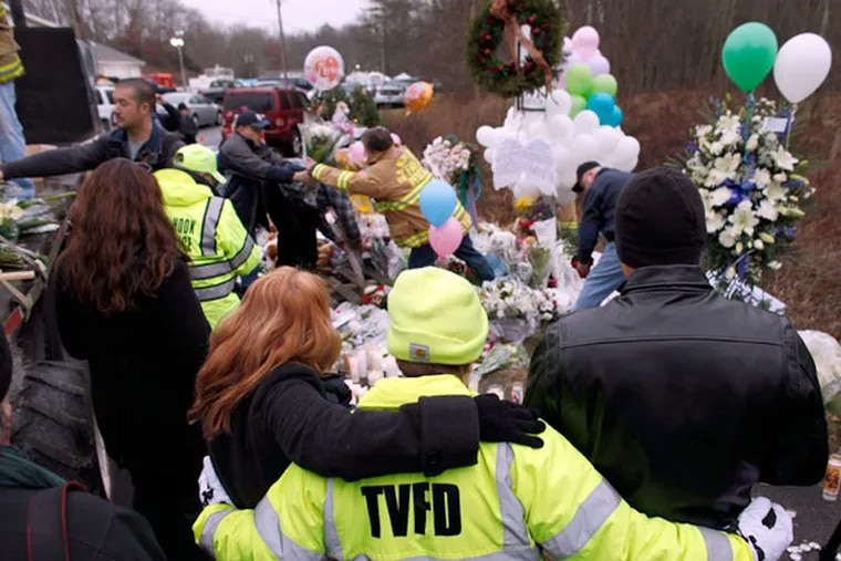 Onlookers embrace as firefighters and other volunteers reorganize a memorial for shooting victims near Sandy Hook Elementary School before erecting a shelter over it, Sunday, Dec. 16, 2012 in Newtown, Conn.  A gunman walked into Sandy Hook Elementary School in Newtown on Friday and opened fire, killing 26 people, including 20 children. (AP Photo/Jason DeCrow)