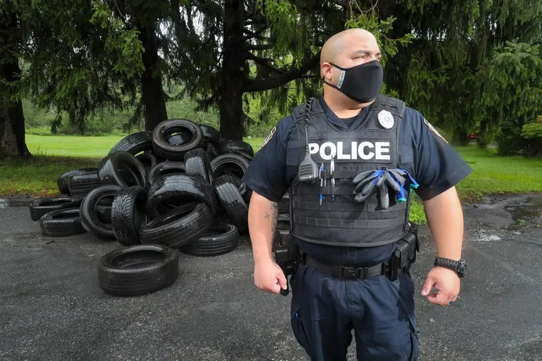 Officer A. Cruz of the Monroe County Waste Authority Police Department surveys an illegal dump of used tires along Route 611 in Pocono Township, Pa.