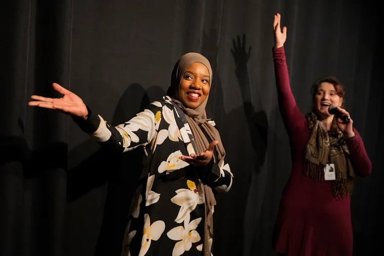 """Ameenah Muhammad-Diggins (left), a local Philly author, and Danielle Defassio, manager of studio and performing arts at the Please Touch Museum, gesture toward the actors after a members-only performance of Muhammad-Diggins' story, """"Bashirah and the Amazing Bean Pie."""""""