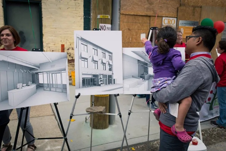 A man and his daughter look at building plans for the new South Philly Food Co-op, where'll be a member-owner.