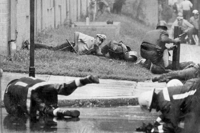 Police and firefighters duck after others were hit by gunfire at the start of the Aug. 8, 1978, shoot-out. Officer James Ramp was killed and many others were injured.