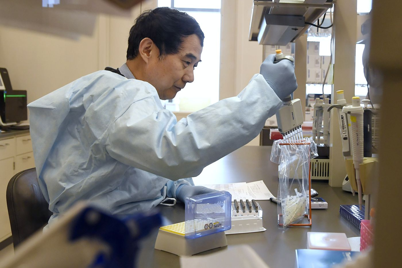 Microbiologist Xiugen Zhang runs a Polymerase Chain Reaction, or PCR, test at the Connecticut State Public Health Laboratory.