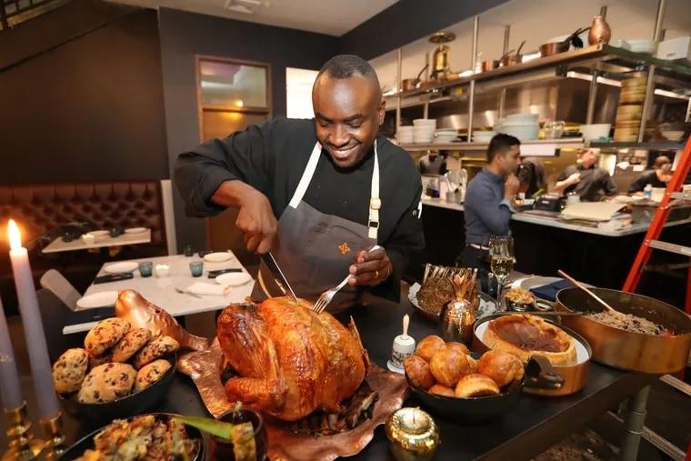 Chef Sylva Senat cuts the Thanksgiving turkey at Maison 208. DAVID SWANSON / Staff Photographer