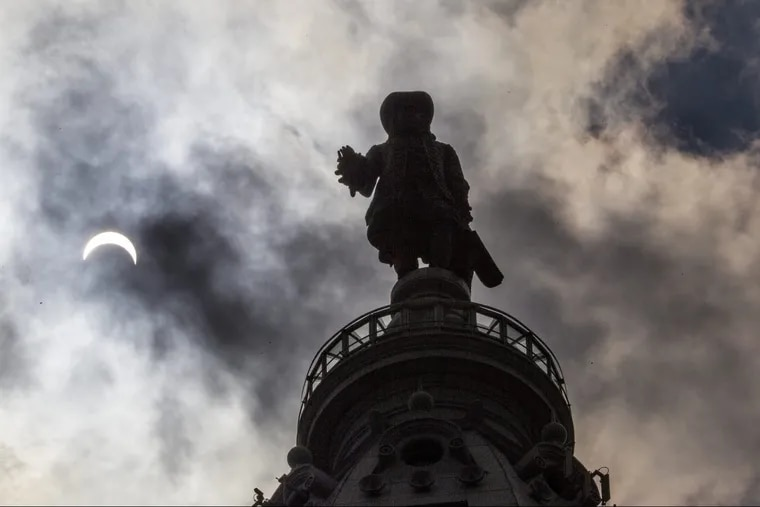 The statue of William Penn atop City Hall is silhouetted by the solar eclipse on Aug. 21.