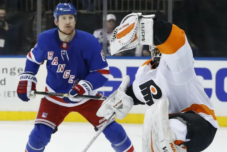 New York Rangers left wing Cody McLeod (8) watches as Philadelphia Flyers goaltender Alex Lyon (49) makes a glove save in the second period of an NHL hockey game in New York, Sunday, Feb. 18, 2018.