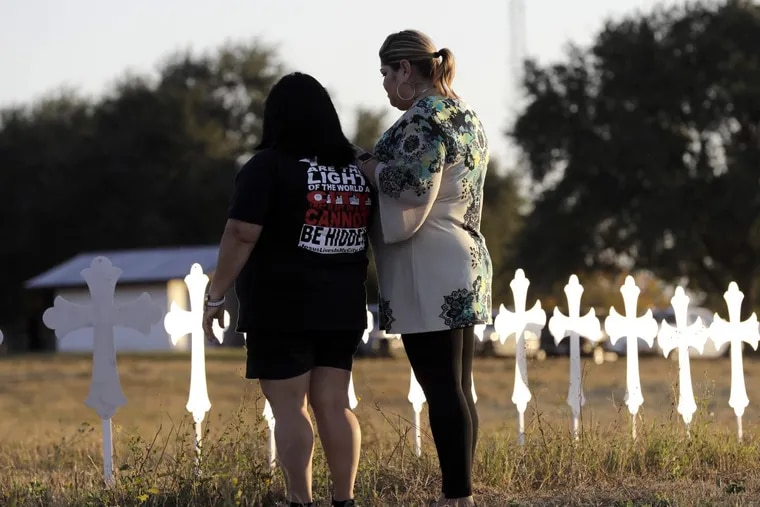Laura Torres, right, and Sonia Yanez visit a line of crosses before a vigil for the victims of Sunday's First Baptist Church shooting, Monday, Nov. 6, 2017, in Sutherland Springs, Texas.