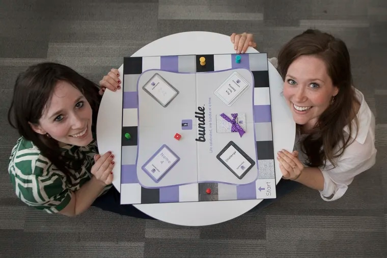 Cassie (left) and Jacklyn Collier with their board game Bundle, intended to bring friends and families together with nostalgia.