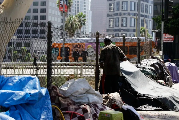 """A man stands in a homeless camp in Los Angeles as police clear the way for a motorcade for President Donald Trump last week. Trump began a California visit by saying he will do """"something"""" about homelessness."""