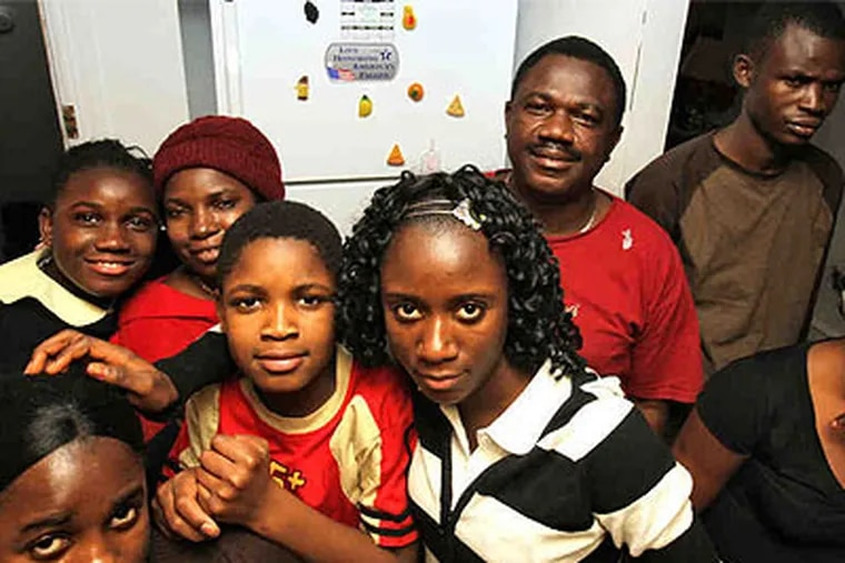 A family reunited: Baindu (front left), 20, and (left to right) Marie, 14; mother Sarah; Mark, 12; Amelia, 18; father James; and John, 25, in the kitchen of the Kettor home. Elizabeth, 24, and James Kettor Jr. are not pictured. (David M Warren / Staff Photographer)