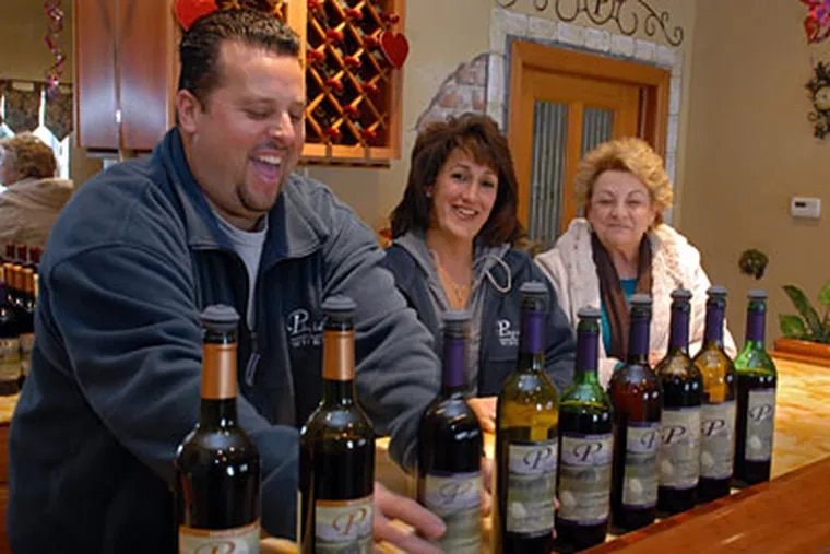 Ollie, Cory, and his mother, Concetta Tomasello, with some of the wines made at Plagido's, where production began in 2007. (TOM GRALISH / Staff Photographer)