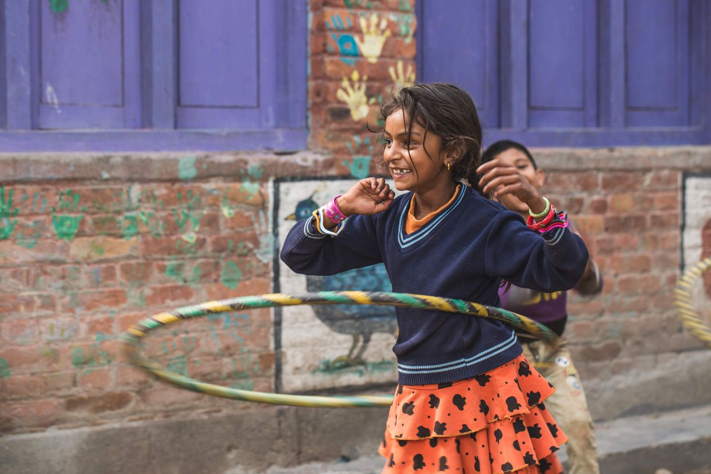 Laxmi, 8, plays with a Hula-Hoop at the Happy Kids Center. She is the first member of her family ever to attend school, as well as the first member of her family not to engage in child labor.