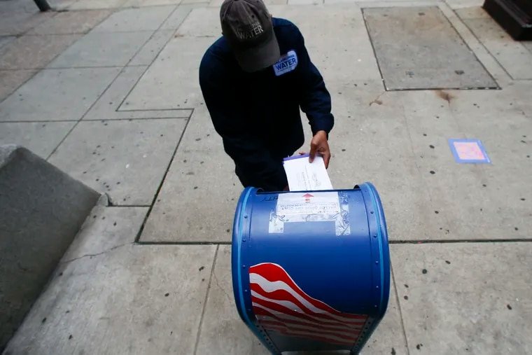 A voter drops a ballot into a mail ballot drop box outside City Hall in May.