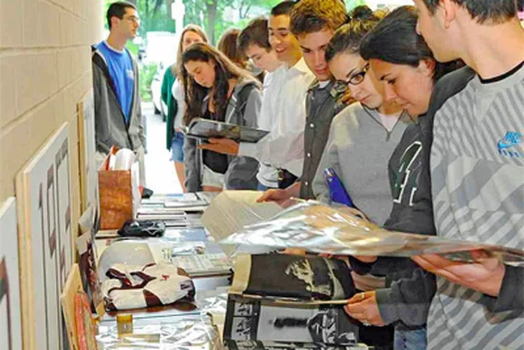 Lower Merion High School students examine time-capsule items - both those from 1910 and current items to be left for students to examine similarly decades from now. (Clem Murray / Staff Photographer)