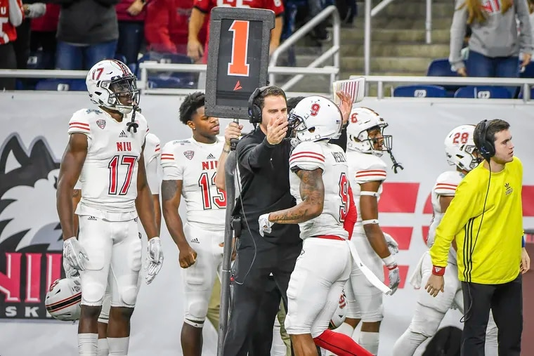 Northern Illinois offensive coordinator Mike Uremovich (middle) congratulating one of his players this past season.