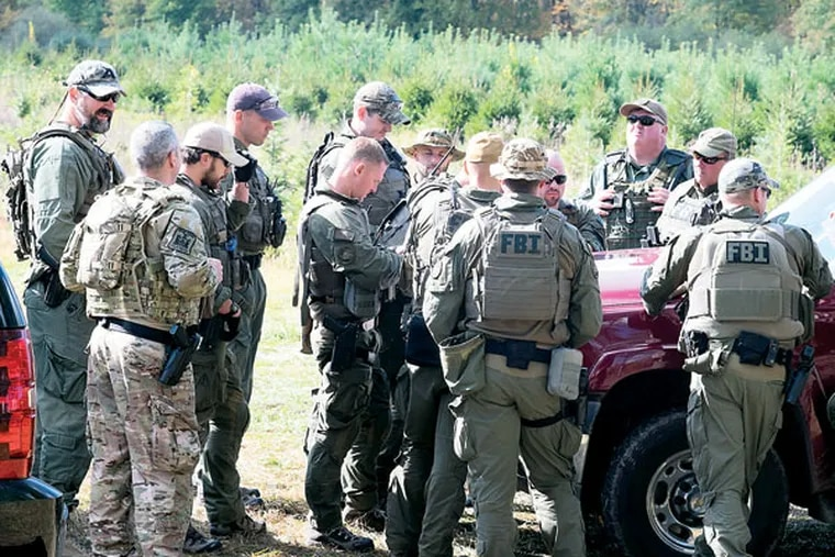 FBI agents gather Wednesday, Oct. 8, 2014, for a briefing in Canadensis on the continued search for Eric Frein. ( ED HILLE / Staff Photographer )