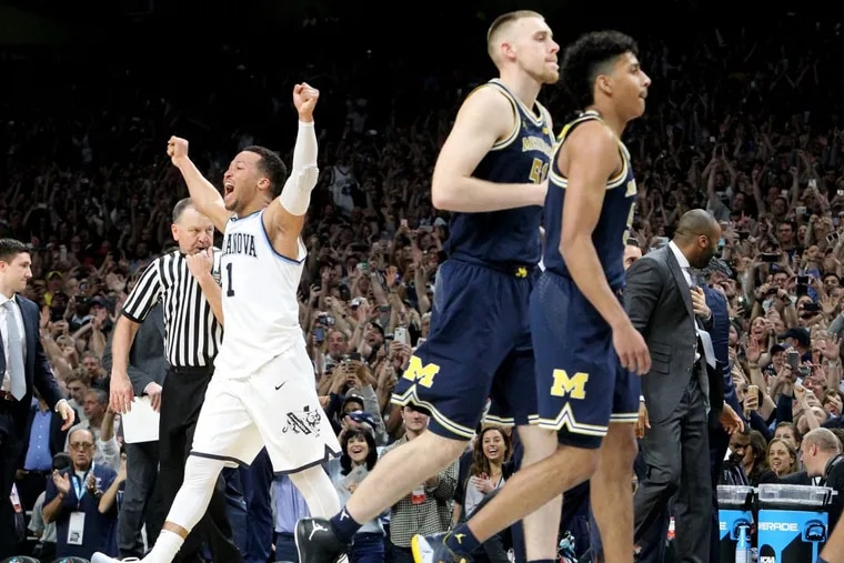 Jalen Brunson, left, of Villanova raises his arms at the end of the game as Michigan players walk off in the National Championship game of the NCAA Tournament at the Alamodome on April 2, 2018.
