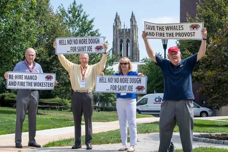 From left, St. Joe's alumni, Jim Henwood and Chris Lehman; Maureen Lehman, Chris' wife who is not a a St. Joe's alumna; and Joe Henwood, an alumnus, hold signs to protest the university's removal of a professor and what they said was an increasing move toward the far left.