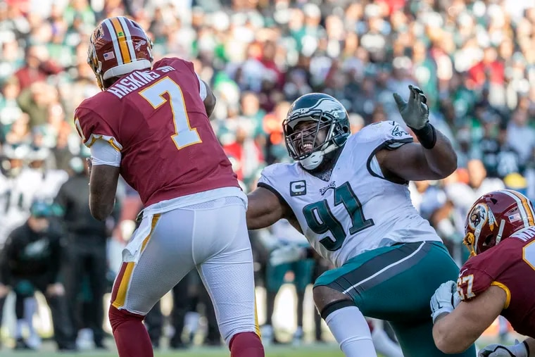 Eagles defensive tackle Fletcher Cox, right, does his best to pressure Washington quarterback, Dwayne Haskins, left, during the thrid quarter.