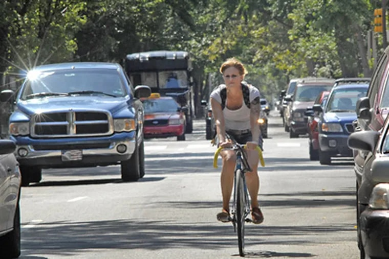 On Pine Street near 16th, bicyclist Melissa Kistler of Philadelphia shares the street with motorists and delivery trucks on her way to work.  (April Saul / Staff Photographer)