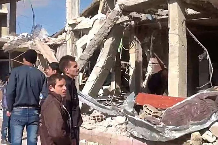 Syrians gather in front of a building destroyed by a car bomb in Qatana, 15 miles southwest of Damascus. State media reported Thursday that bombs had exploded in two suburban districts, killing 24 and wounding dozens. SANA, AP