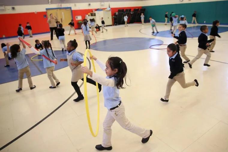 Kindergarten students run around during recess in the gymnasium at Camden's Pride Charter School in Camden, N.J., on Wednesday.