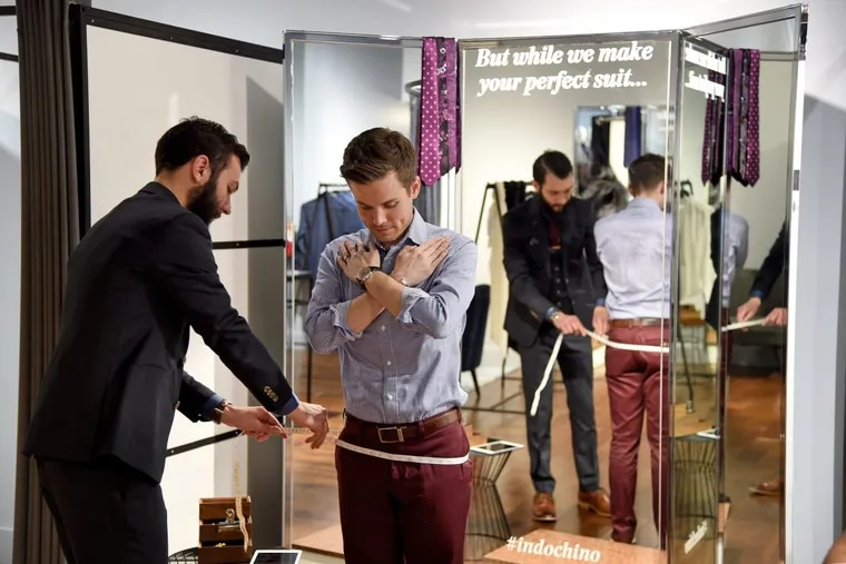 indochino Style Guide Michael Prevete (left) demonstrates how he measures a customer, using showroom manager Quinn Quinsler (right) at Indochino on Chestnut Street on Tuesday. The online retailer will add 18 showrooms next year throughout the U.S.