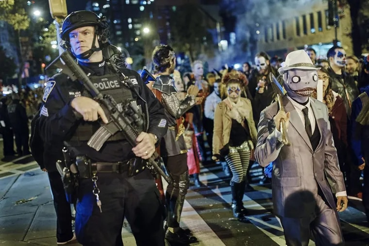 Heavily armed police guard as revelers march during the Greenwich Village Halloween Parade, Tuesday, Oct. 31, 2017. New York City's always-surreal Halloween parade marched on Tuesday evening under the shadow of real fear, hours after a truck attack killed several people in what authorities called an act of terror.