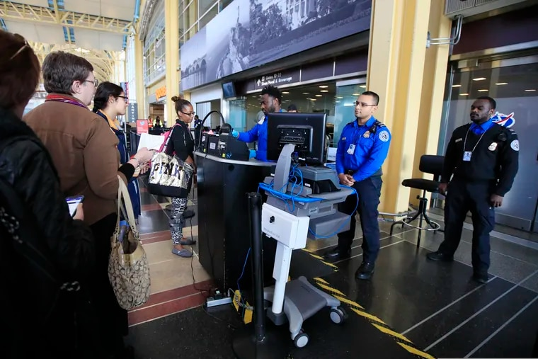 Transportation Security Administration (TSA) officers check and watch airline passengers at Reagan National Airport in Washington, Thursday, Dec. 27, 2018. TSA employees are working through the partial government shutdown without pay.