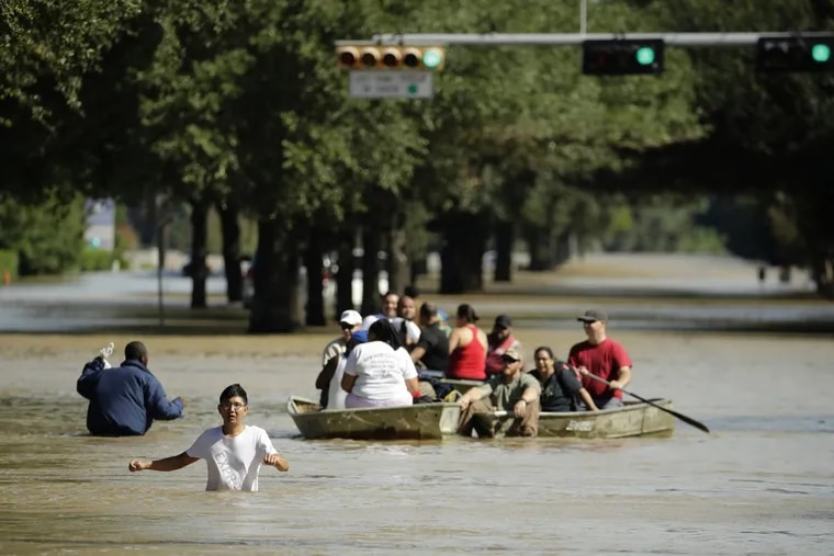 Residents used a boat to evacuate a Houston neighborhood inundated by water after Hurricane Harvey.