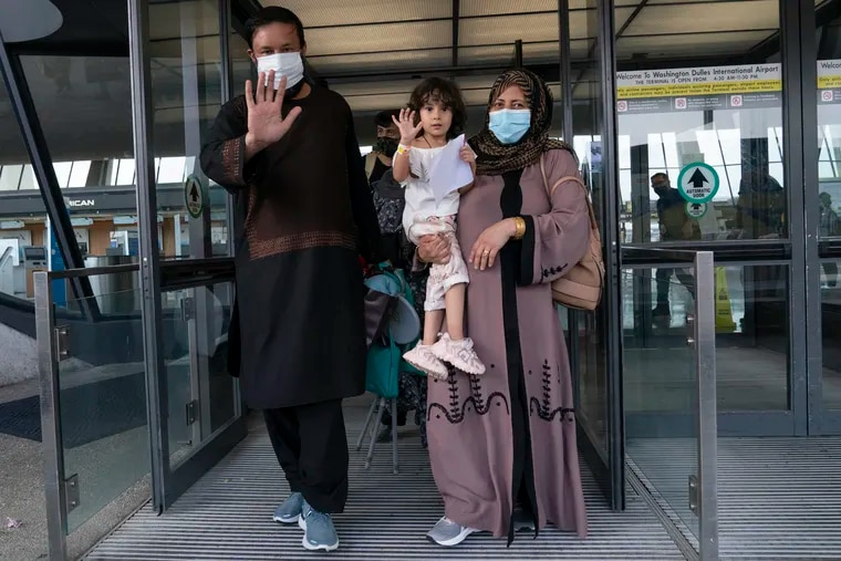Families evacuated from Kabul, Afghanistan, walk through the terminal before boarding a bus after they arrived at Washington Dulles International Airport, in Chantilly, Va., on Monday, Aug. 30, 2021.