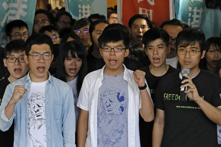 """From front left, Hong Kong activist Nathan Law, Joshua Wong and Alex Chow were found guilty of leading or encouraging an illegal rally in September 2014 that kicked off the demonstrations known as the """"Umbrella Movement."""""""